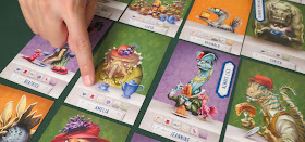 A close-up of some of the cards laid out in a grid. A few examples that can be seen include Amelia, a leptoceratopsian dinosaur wearing an light olive green dress and a red hat with purple flowers, looking somewhat grumpy as she sits at a table with a kettle of tea and a teacup; and Jeannine, a blue dilophosaurus in a forest green outfit wearing a small red hat adorned with black feathers, lots of gold necklaces glasses, and lipstick, holding a large gelatin, with a small feathered pink dinosaur on the table beside her. Someone is pointing to one of the icons on Amelia's card, and a token that says 'Always Lies' has been placed on Jeannine's card.