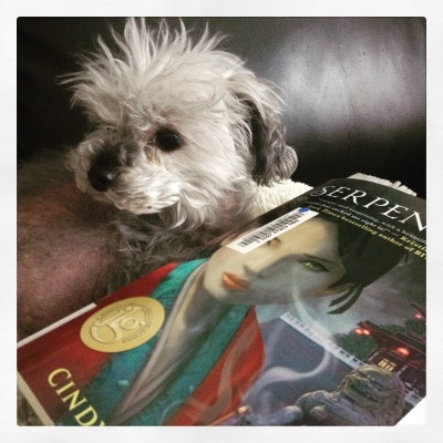 Murchie curls up beside a trade paperback copy of Serpentine, his head raised as he looks at something beyond the frame. Serpentine's cover features a girl of Asian descent, her face close to the viewer and a walled building with a lion statue in front of it visible over her shoulder.