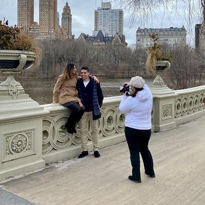 Photographer taking a photo of a couple on Bow Bridge