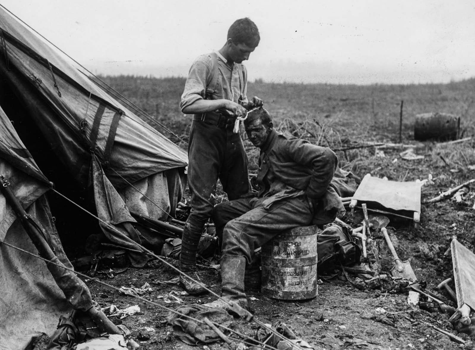 A British soldier dresses the wounds of a German prisoner near Bernafay Wood. July 19, 1916.