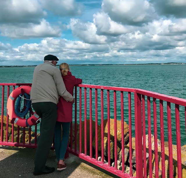 Una coppia romantica osserva il mare dal pontile sottostante al faro di Howth