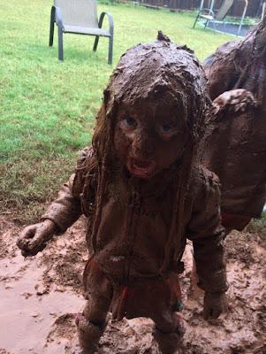 Witziges Kind spielt im Sommerregen im Garten - Schlamm lustig
