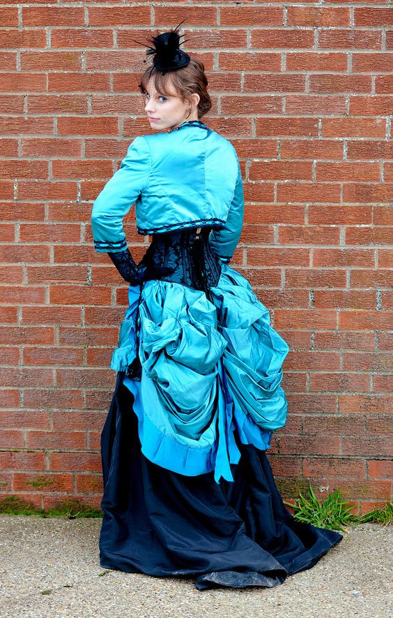 Steampunk Woman wearing turquoise and navy blue skirt, corset, bolero jacket, gloves and top hat fascinator with birdcage veil