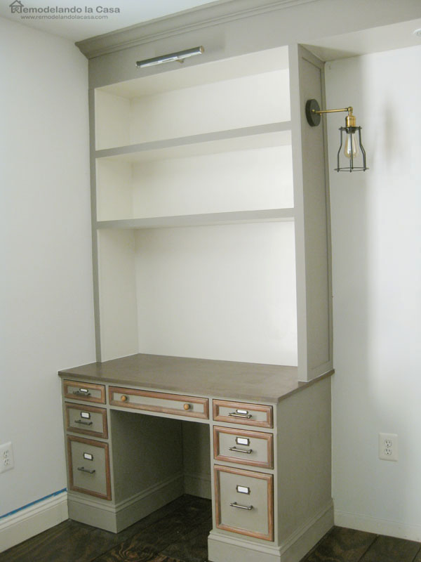 grey and white built-ins with desk area  and picture frame lighting and sconces.
