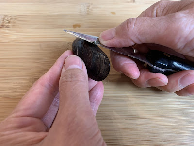 Mussels being debeard with a knife