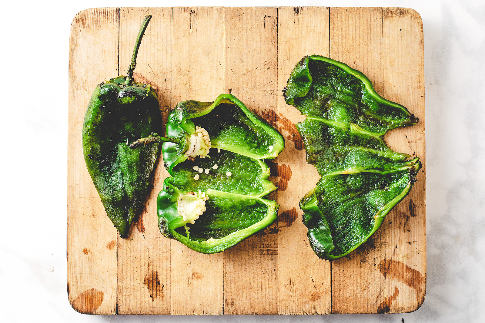 The steps to removing seeds from a roasted poblano pepper.
