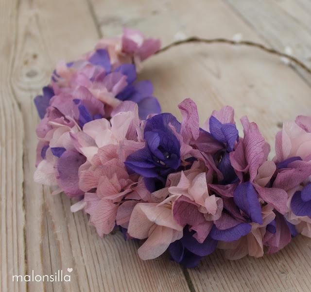 Vita de la corona PUENTEDEY en detalle de flores preservadas en color morado para invitada boda sobre fondo de madera