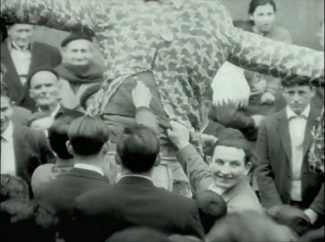 Imagen de 'Lejos de los árboles (1972)' - Hombres desvisten al Judas y lo rellenan con petardos en la Plaza Mayor