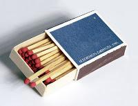 Ağzı açık mavi bir kibrit kutusu içindeki kırmızı başlıklı kibrit çöpleri