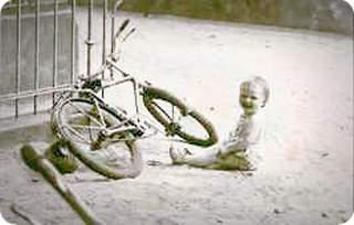 Ich im Alter von 2 Jahren im Sand vor einem abgelegten Fahrrad direkt an der Kurbel sitzend.