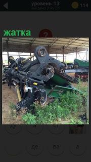 Под крышей в ангаре стоит сельскохозяйственная машина жатка