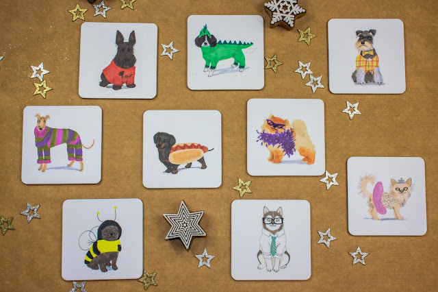 9 coasters with different dog illustrations on including a pug in a bee suit, husky in a suit, a sausage doll in a roll and springer spaniel in a dragon costume.