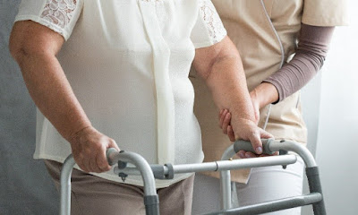 elderly women with walker assisted by a home health aide
