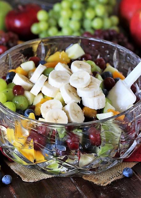 Adding Sliced Bananas to Peach Pie Filling Fruit Salad Image