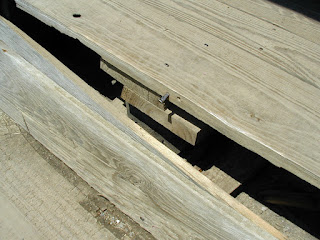 a square nail partially protruding from the wood floor plank