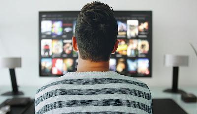Seorang yang menonton streaming online film dengan smart TV
