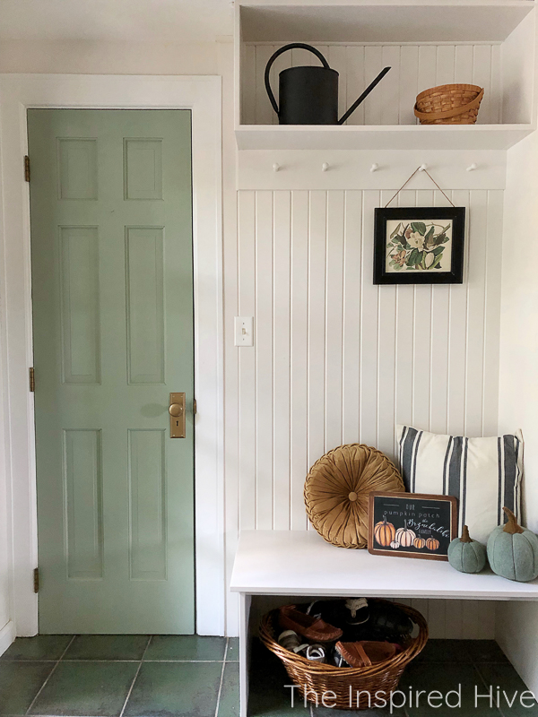 Farmhouse mudroom decorated for fall. Green door, tongue and groove wall, and peg rail hooks.