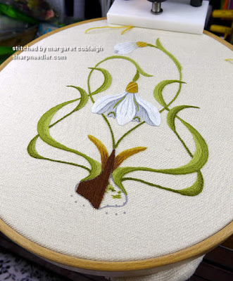 Dark brown laidwork being embroidered on bulb at bottom of crewel snowdrops