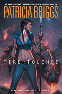 Cover image description: Mercy Thompson wears a blue tank top and jeans while holding a spear. Behind her there's a menacing-looking dog made out of cooling lava.