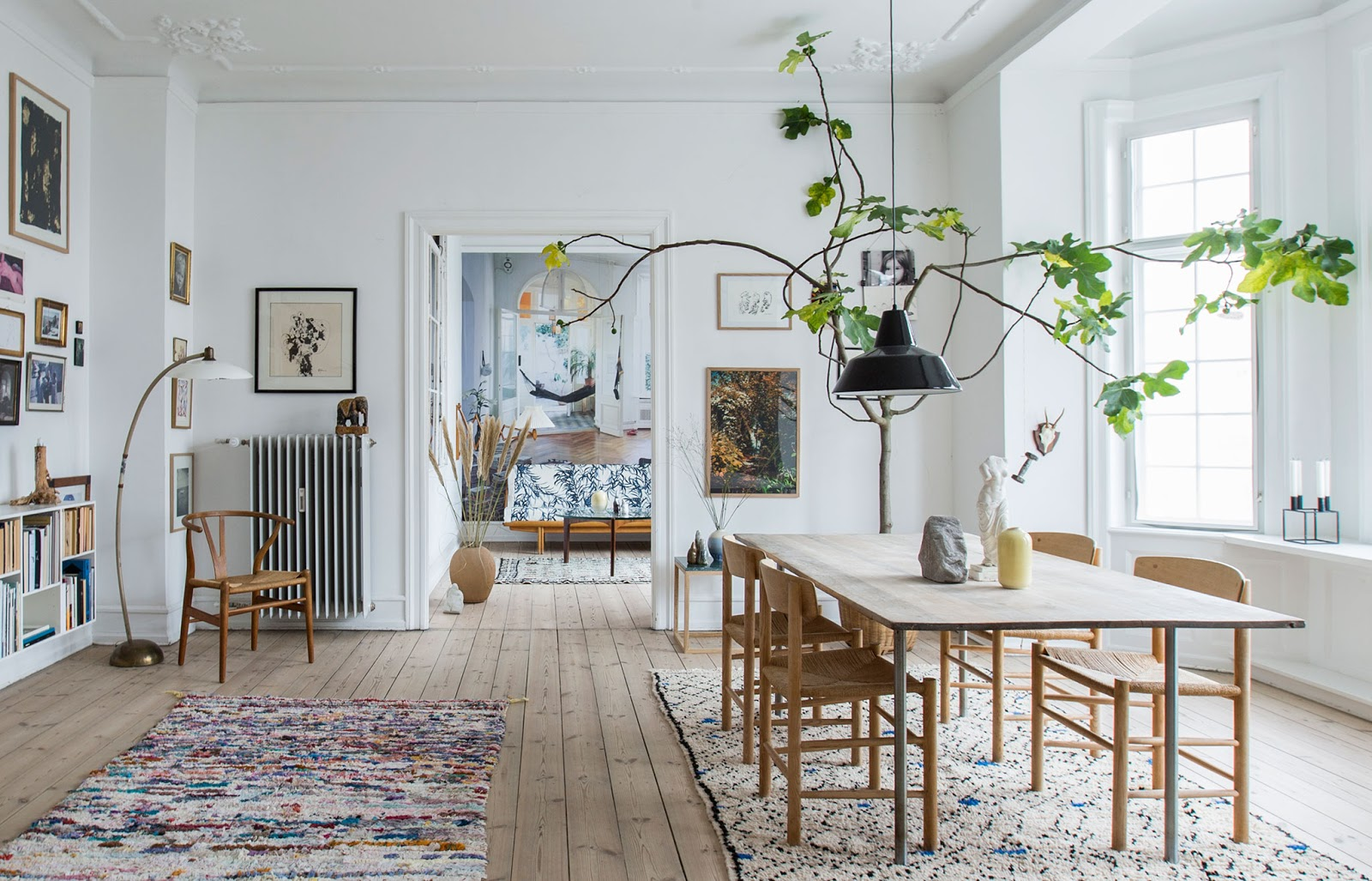 bohemian scandinavian apartment with moroccan rugs, wall art and design furniture, houseplants, hans wegner chair