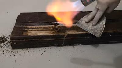 بشبوري لهب يخرج منه نار موجه على قطعة من الخشب و إزالة الدهان بمساعدة سكين