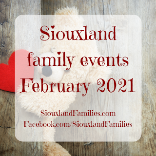 """in background, a khaki colored teddy bear holds a red paper heart against a faux wood background. in foreground, the words """"Siouxland family events February 2021"""""""