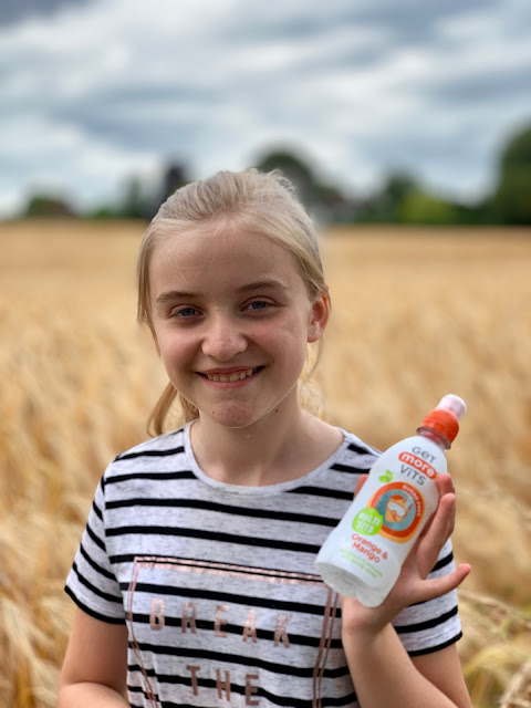 girl in barley field with Get More Vits drink