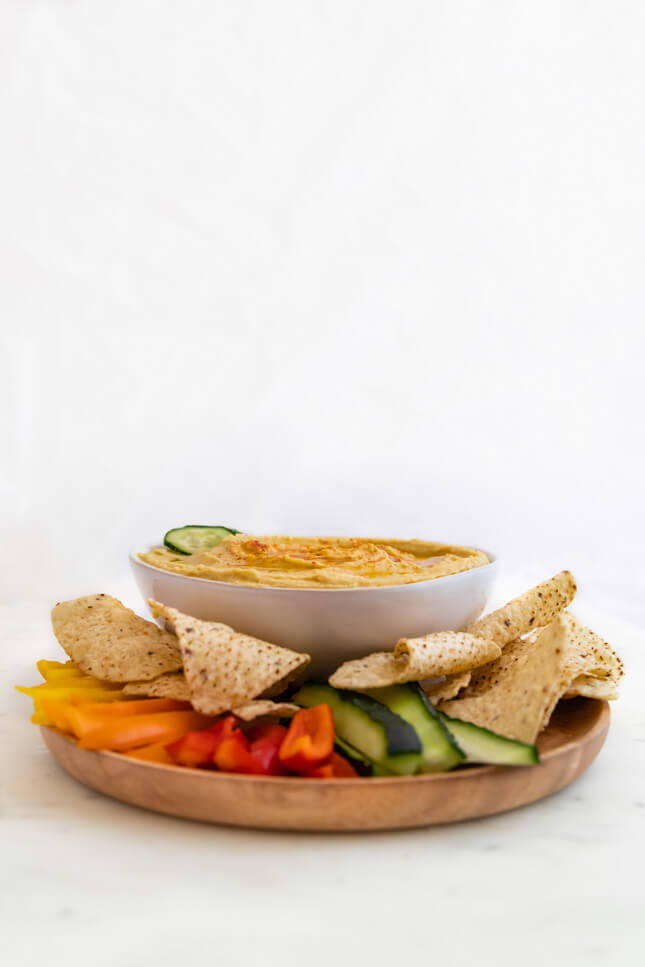 Profile photo of a bowl of hummus decorated with crudités