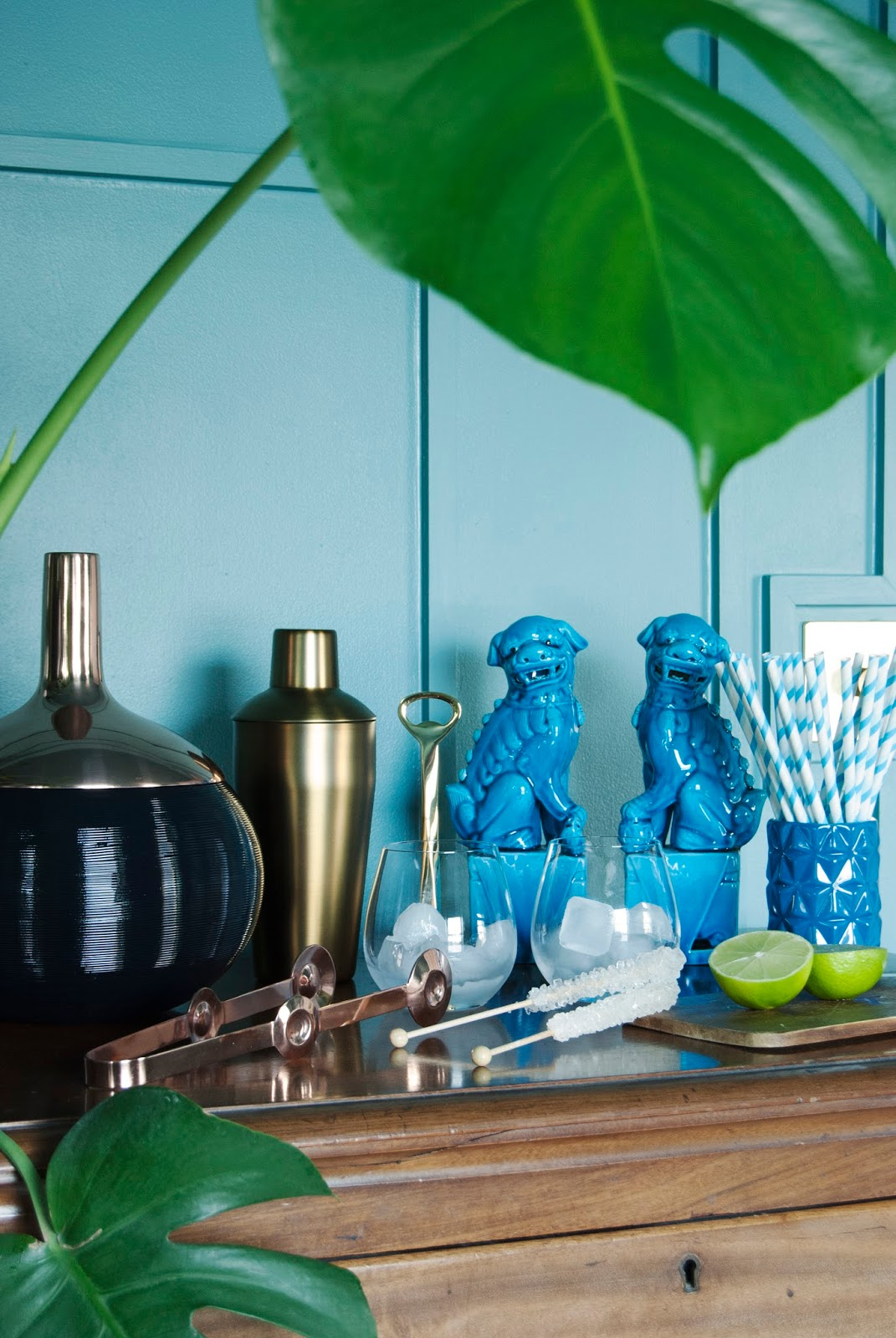 Amara Shoppable Home Inspiration Pages - French For Pineapple Blog - Teal blue decorative moulding with bar set up, gold and brass with turquoise foo dogs and monstera leaves
