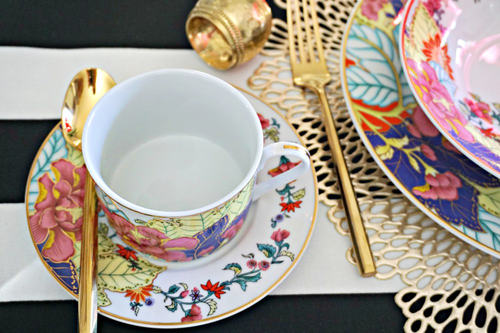 Imperial leaf tobacco leaf china tea cup and saucer set a top a black and white tablecloth for a stylish placesetting.