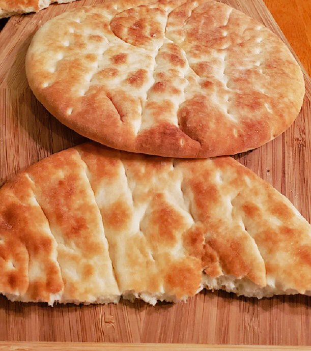 a photo of pita bread cut in half and whole