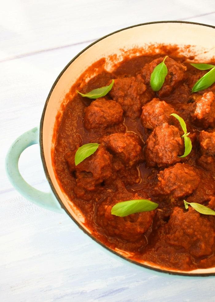 vegan 'meatballs' in marinara sauce in a shallow, blue casserole pan