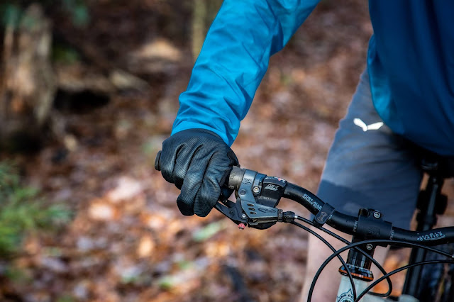 Tight shot of a mountain biker from the elbows down seen with his right hand on the brake, wearing the GORE stretch Mid gloves, with a blurred background of fallen leaves on a trail in the woods.
