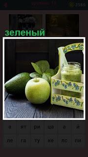 на столе лежат яблоки и зеленый сок приготовленный из них