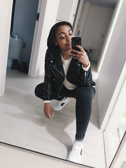Crouched wearing light wash black jeans, star embroidered sneakers, cream sweater, and black vegan leather jacket with silver star embroidered taken in a mirror