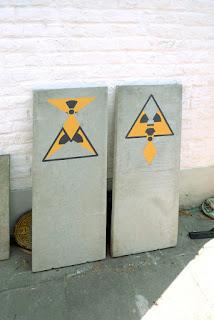 Deux stèles en béton (40 sur 100 cm) posées contre un mur blanc avec le symbole de la radioactivité peint, détourné de deux manières différentes
