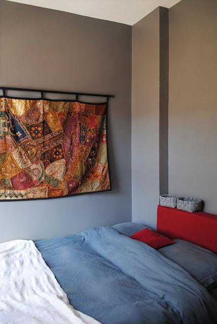 Hoek van de slaapkamer met grijze muren en een bohemien wandkleed.