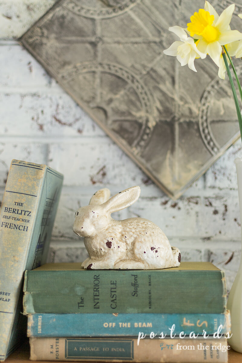 cast iron bunny statue on top of old books