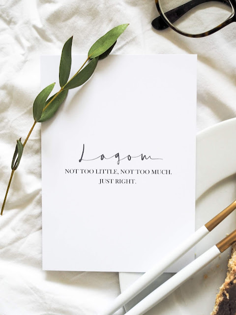 Card that reads 'Lagom, not too little, not too much, just right', set against a cake plate and flower