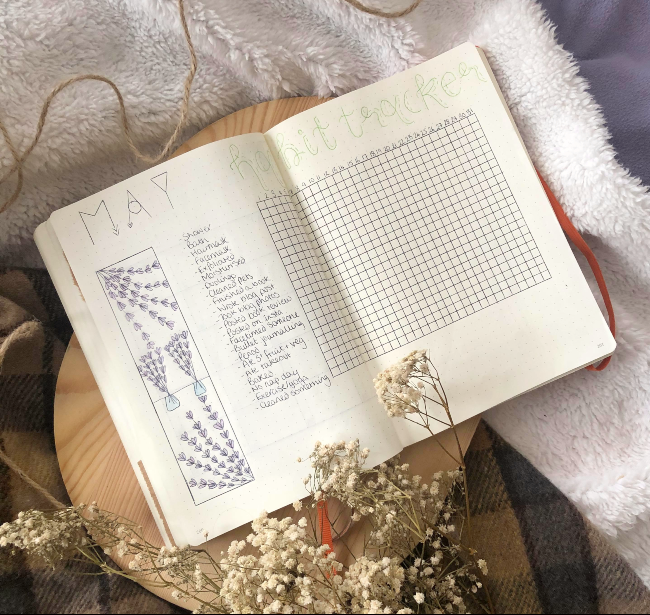 Double page in a dotted journal with a strip of lavender bouquets to the left and a habit tracker rectangle to the right