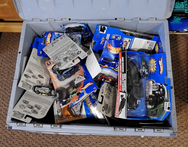 A tote box full of hot wheels toys for sale, many in the original package and never opened.