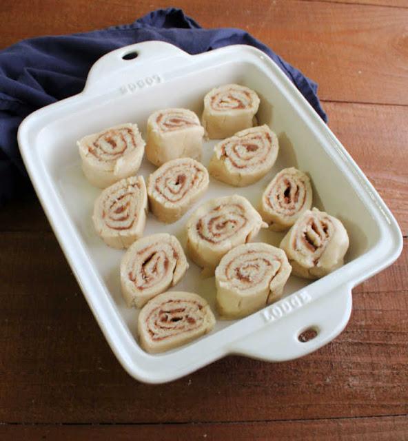 raw cinnamon roll-like butter rolls in pan waiting for warm milk mixture