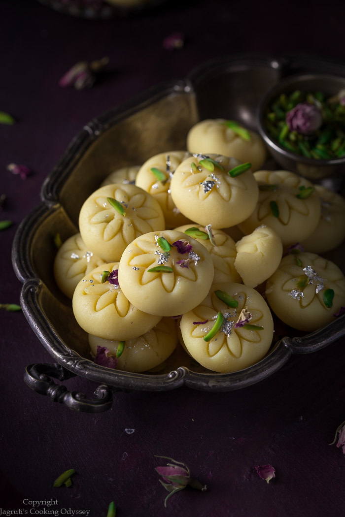 mawa peda arranged in a metal tray and garnished with pistachio slivers