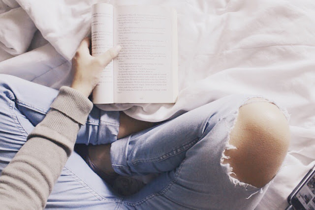 Woman reading a book in bed style ripped jeans
