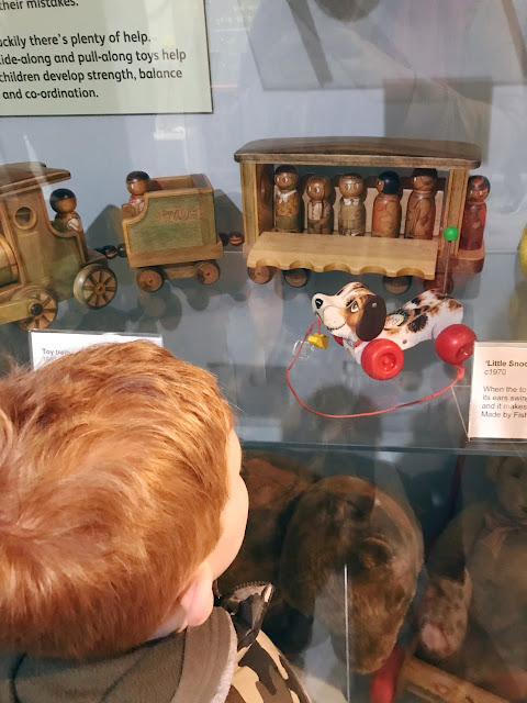 Boy looking at display case holding vintage toys