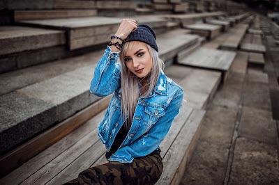 Precio chica rubia con gorro y chaqueta vaquera sentada en un banco