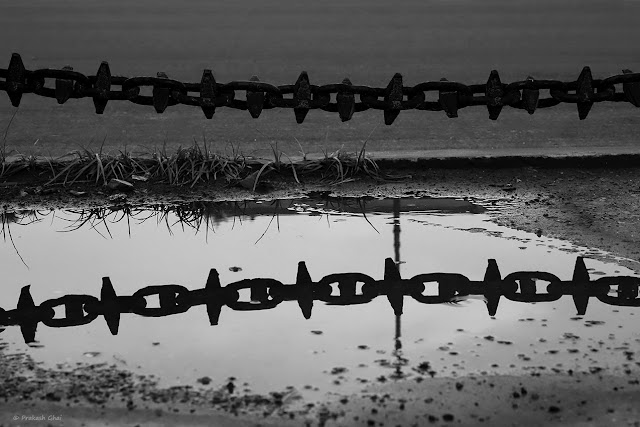 A Black and White Minimal Art Photograph of the Reflection of a Metal Chain in Water.