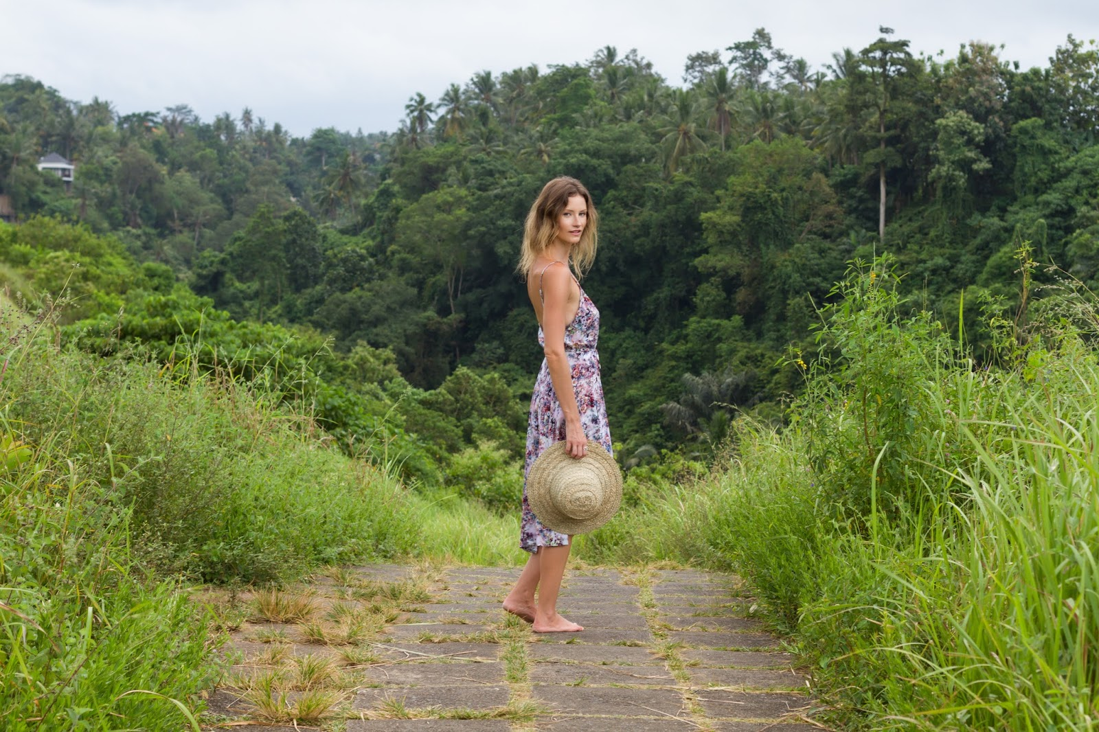 Fashion and travel blogger, Alison Hutchinson, is wearing a floral print bohemian KAYVALYA dress at the Ridge Walk in Ubud, Bali