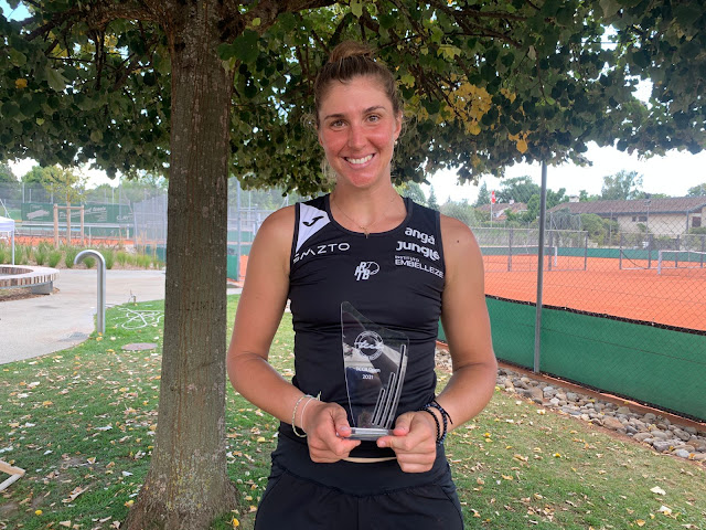 Em frente a uma árvore, com quadras de tênis ao fundo, Bia Haddad sorri com título