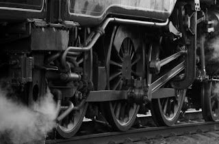 A black and white closeup of the wheels of a steam locomotive.